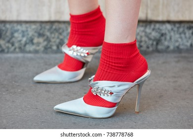 MILAN - SEPTEMBER 21: Woman with silver high heel shoes with gems decoration and red socks before Prada fashion show, Milan Fashion Week street style on September 21, 2017 in Milan.