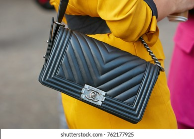 MILAN - SEPTEMBER 22: Woman with black Chanel leather bag and yellow dress before Versace fashion show, Milan Fashion Week street style on September 22, 2017 in Milan.