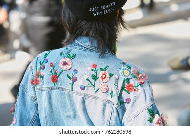 MILAN - SEPTEMBER 22: Woman with blue jeans jacket with floral decorations before Giorgio Armani fashion show, Milan Fashion Week street style on September 22, 2017 in Milan.