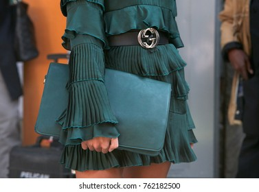 MILAN - SEPTEMBER 22: Woman with dark green dress and bag and Gucci belt before Giorgio Armani fashion show, Milan Fashion Week street style on September 22, 2017 in Milan.