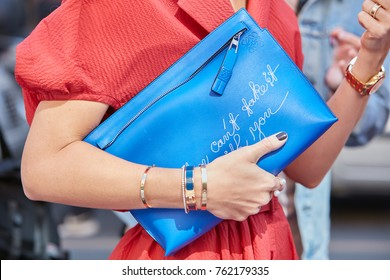 MILAN - SEPTEMBER 22: Woman with golden Cartier bracelets and blue leather Loewe bag before Sportmax fashion show, Milan Fashion Week street style on September 22, 2017 in Milan.