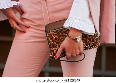 MILAN - SEPTEMBER 22: Woman with Louboutin bag with studs before Prada fashion show, Milan Fashion Week street style on September 22, 2016 in Milan.