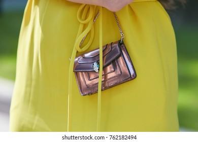 MILAN - SEPTEMBER 22: Woman with metallic iridescent Bulgari bag in pink with yellow dress before Giorgio Armani fashion show, Milan Fashion Week street style on September 22, 2017 in Milan.
