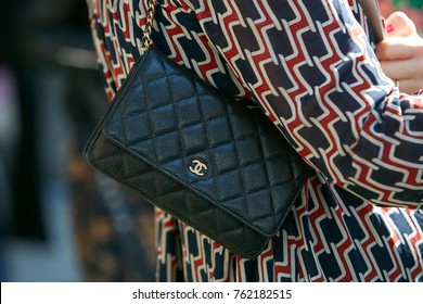 MILAN - SEPTEMBER 22: Woman with small Chanel black leather bag with golden logo before Giorgio Armani fashion show, Milan Fashion Week street style on September 22, 2017 in Milan.