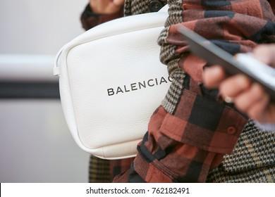 MILAN - SEPTEMBER 22: Woman with white Balenciaga bag and brown tones sleeve before Giorgio Armani fashion show, Milan Fashion Week street style on September 22, 2017 in Milan.