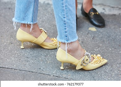 MILAN - SEPTEMBER 22: Woman with yellow high heel decorated shoes and torn blue jeans before Sportmax fashion show, Milan Fashion Week street style on September 22, 2017 in Milan.