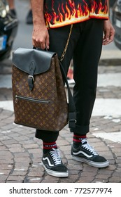 MILAN - SEPTEMBER 23: Man with Louis Vuitton backpack and shirt with flames before Antonio Marras fashion show, Milan Fashion Week street style on September 23, 2017 in Milan.
