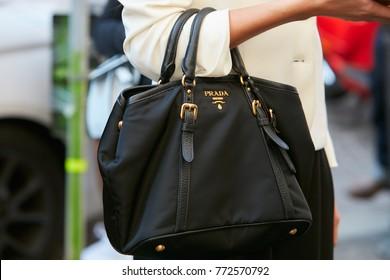 6f8e9c5d248e15 MILAN - SEPTEMBER 23: Woman with black Prada bag with golden logo and white  jacket