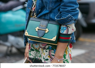 MILAN - SEPTEMBER 23: Woman with green Prada bag and blue jeans jacket before Antonio Marras fashion show, Milan Fashion Week street style on September 23, 2017 in Milan.
