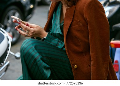 MILAN - SEPTEMBER 23: Woman with green silk trousers, brown jacket looking at smartphone before Antonio Marras fashion show, Milan Fashion Week street style on September 23, 2017 in Milan.