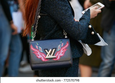 MILAN - SEPTEMBER 23: Woman with Louis Vuitton bag with pink and blue flames looking at smartphone before Blumarine fashion show, Milan Fashion Week street style on September 23, 2017 in Milan.