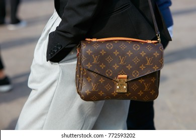 MILAN - SEPTEMBER 23: Woman with Louis Vuitton bag with black jacket and gray trousers before Gabriele Colangelo fashion show, Milan Fashion Week street style on September 23, 2017 in Milan.