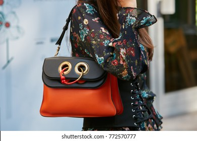 MILAN - SEPTEMBER 23: Woman with orange and black leather bag and floral dress before Blumarine fashion show, Milan Fashion Week street style on September 23, 2017 in Milan.