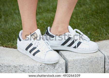MILAN - SEPTEMBER 23: Woman with white Adidas superstar sneakers before Giorgio Armani fashion show, Milan Fashion Week street style on September 23, 2016 in Milan.