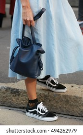 MILAN - SEPTEMBER 25: Woman with blue leather Loewe bag and Vans shoes before Salvatore Ferragamo fashion show, Milan Fashion Week street style on September 25, 2016 in Milan.