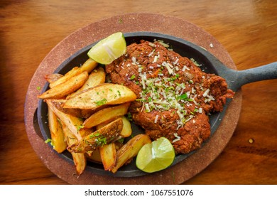 Milanese of lamb meat accompanied by French fries in a decorated frying pan on a restaurant table.