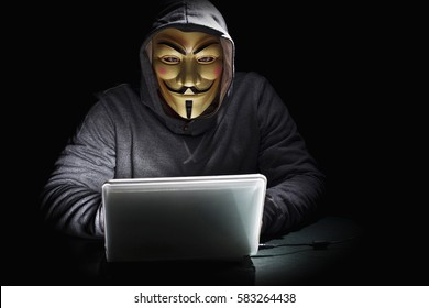 MILAN,ITALY, February, 2017: Hacker wear anonymus mask with notebook in the dark .Editorial photo.