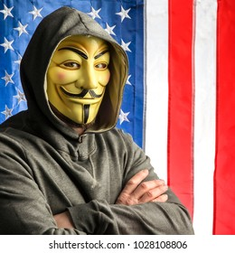 MILAN,ITALY, February, 2018: Hacker crossing arms wear anonymus mask with american old glory flag in background.Editorial photo.