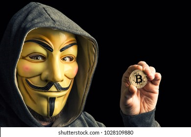 MILAN,ITALY, February, 2018: Hacker hold golden bitcoin coin and  wear anonymus mask .Editorial photo.