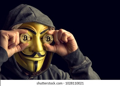 MILAN,ITALY, February, 2018: Hacker old bitcoin coin and wear anonymus mask .Editorial photo.