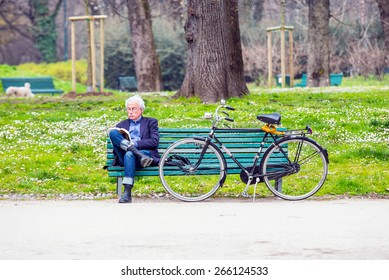 MILAN,ITALY - MARCH 24, 2015:Man sitting on the bench in the Sempione park reading book