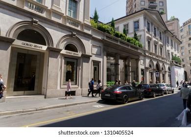 Milan,Italy - May 12 2018: Via Monte Napoleone upscale shopping street. Window shopping crowd outside Giorgio Armani & Louis Vuitton Milano fashion district famous shops & high end exclusive boutiques