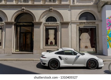 Milan,Italy - May 12 2018: Via Monte Napoleone upscale shopping street with luxury car. Window showcase of Milano fashion district Louis Vuitton shop with a white Porsche car parked outside.