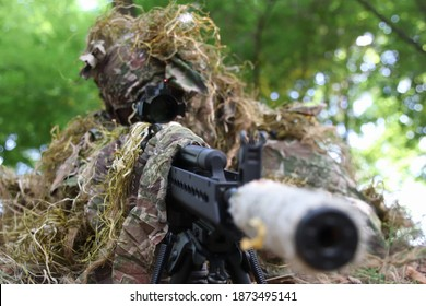 milan,italy,5 september 2020 sniper with ghillie suite taking aim with his ak custom in  a forest not far from the city