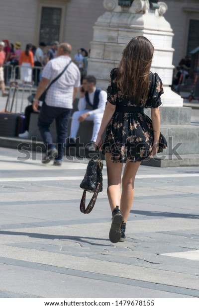 Milano, Italy - 21.6.2019: Beautiful young woman well dressed and walking shopping in Milan with blurred background. Fashion lady girl in black dress with sexy legs and black bag walking on square.