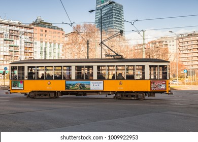 Milano, Italy - January 19, 2018: Yellow tram with ordinary passengers goes on the street on Milano, side view
