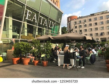 MILANO, ITALY - JUNE, 2018: Milanese people eating and drinking aperitivo at the Eataly Piazza outside and listening to the beats of DJ.