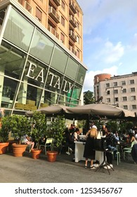 MILANO, ITALY - JUNE, 2018: Milanese people casually eating and drinking aperitivo at the Eataly Piazza outside and listening to the beats of local DJ.