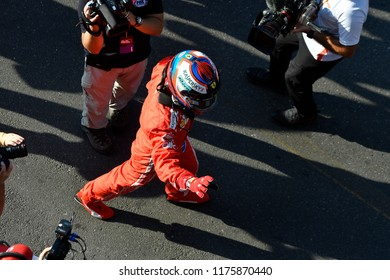 MILANO, ITALY-AUGUST 29, 2018: Ferrari's Formula 1 driver, Kimi Raikkonen, wave to the fans wearing the safety helmet, during the F1 Milan Festival, 2018, in Milan.