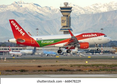 MILANO MALPENSA AIRPORT - November 8, 2016: Airbus A320 of EasyJet Airline Company with Europcar livery land at Milano Malpensa Airport at dawn in a windy day. Control Tower and Alps Mountains.