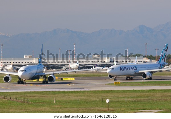 Milano, Malpensa, Lombardy, Italy. About 10/2019. Oman Air Airbus A330-243  airplane on the Malpensa airport runway. In the background the buildings and Air Italy airplane.