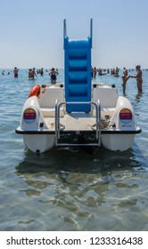 Milano Marittima, Italy - July 14, 2018: Paddle boat and people taking sea bath in the Adriatic Sea atMilano Marittima, a tourist resort on the Adriatic Sea (Romagna region, Italy).
