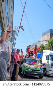 Milano Pride 2018, manifestation of gay, lesbians, asexuals, bisexuals, intersexual and queer pride. Young woman and a man taking selfies during the parade. Milan, Italy. June 30, 2018.