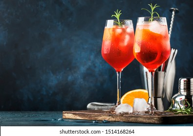 Milano spritzer alcoholic cocktail with red bitter, dry white wine, soda, zest and ice. Dark blue background, bar tools, selective focus