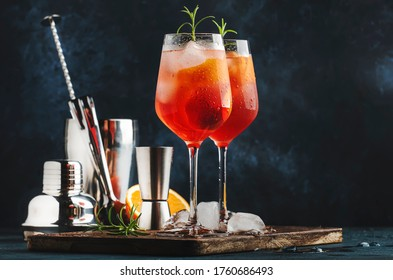 Milano spritzer italian alcoholic cocktail with red bitter, dry white wine, soda, zest and ice. Blue background, steel bar tools, copy space