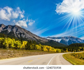 The mild autumn sun illuminates the road to the mountain valley. Rocky Mountains of Canada. Picturesque shores of Abraham Lake. Concept of active, ecological and photo tourism