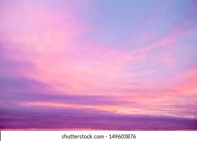 A mild sunset with a pink tint over light blue sky and low hanging clouds.