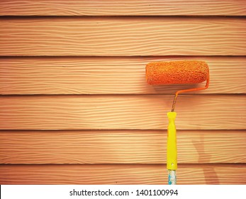 Mild sunshine on surface of the old long handle roller brush with orange shera wood wall background in vintage tone style