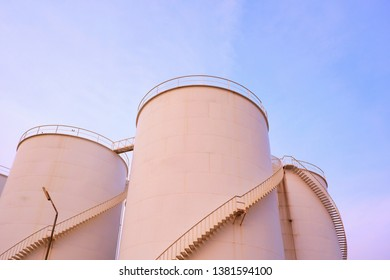 Mild sunshine on surface of storage tanks with spiral staircase against cloud and blue sky background in evening time