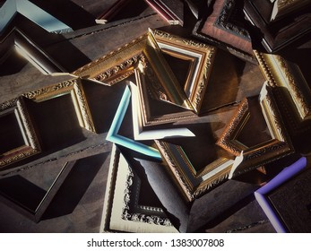 Mild sunshine and shadow on surface of many various patterns of solid wood photo picture frame corner samples on wooden table floor in vintage tone style at workshop in morning time