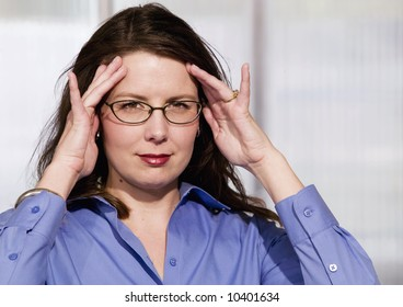 Mildly Frustrated Business Woman with her Hands at her Temples