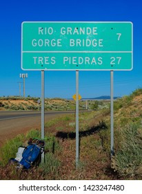Mileage Sign: Rio Grande Gorge Bridge 7 Miles / Tres Piedras, NM 27 on U.S. Highway 64 West with the Photographer's Backpack in the Foreground, Taos, NM/USA (June 12, 2019)