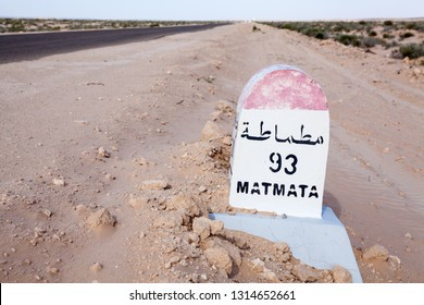 Milepost on a desert asphalt road to the Matmata destination, Tunisia, Africa. Road passing through the salt lake Chott El Djerid. Copyspace