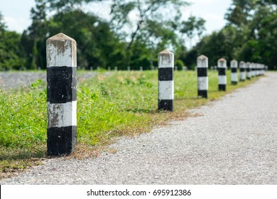 Milestones - Black and white milestones with green grass roadside, Trees roadside in background . concept for next step. Next station.Up level.