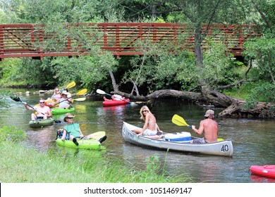 Milford, MI/USA: July 29, 2017 – Summer scene of adults in colorful canoes and kayaks cluster on the Huron River Water Trail, a 104 mile inland paddling trail in the Lower Peninsula of Michigan.