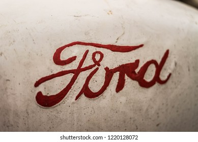MILFORD, OH / USA - October 30 2018: Close up of retro Ford logo painted on an old fashioned rustic American-made Ford N-Series 4 cylinder farm tractor inline engine.